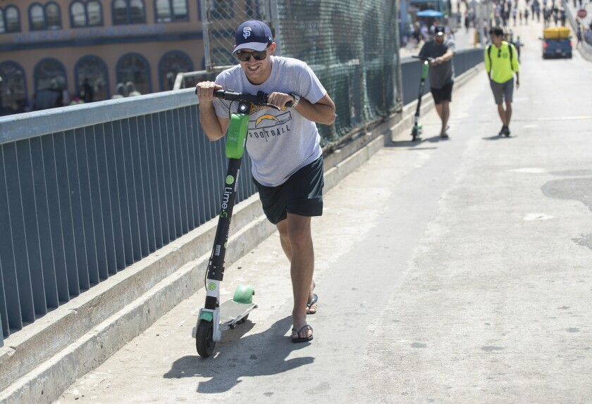 Elliot Stevenson pushes his Lime scooter up the hill from the Santa Monica Pier after a geofence disabled it.