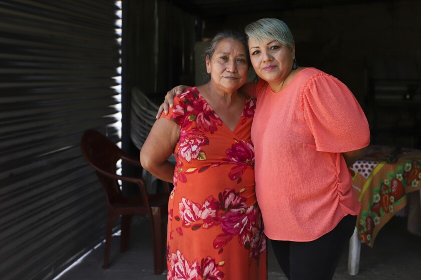 Iris Franco, right, hugs her mother, Elsa Victorina Franco, at her home, in El Ranchador, Santa Ana, El Salvador, Friday, March 5, 2021. The Salvadoran family lives humbly but is in a better place thanks to financial support from a family member in the United States who is part of the Temporary Protected Status program. (AP Photo/Salvador Melendez)