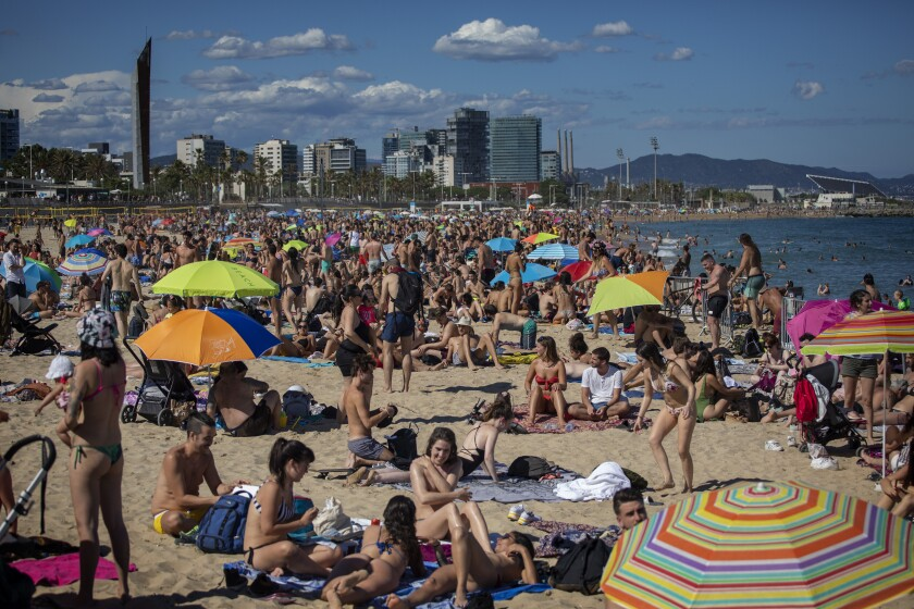 """People enjoy the warm weather on the beach in Barcelona, Spain, Saturday, June 13, 2020. Spanish government has announced that the northwestern region of Galicia will move next week to what the government calls """"the new normal,"""" when some rules, such as wearing face masks when social distancing is not possible, will remain in place. (AP Photo/Emilio Morenatti)"""