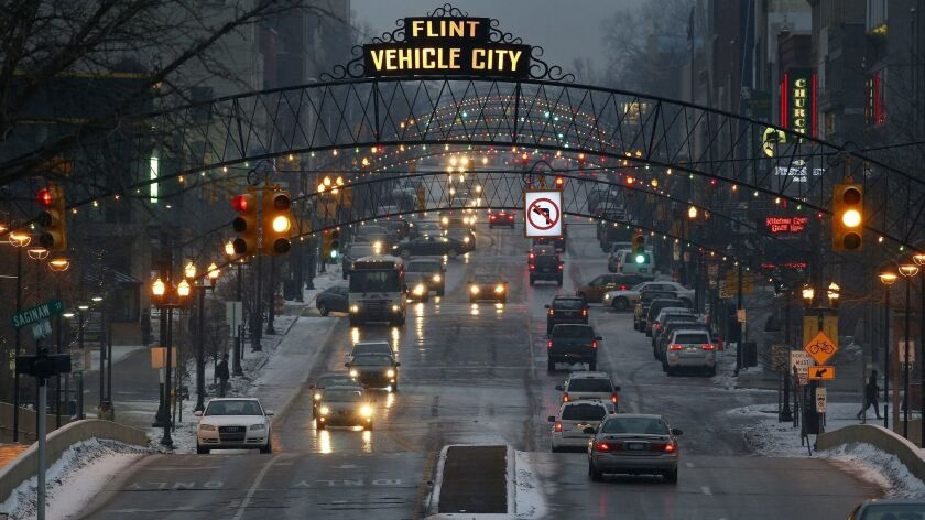 FILE - Vehicles drive through downtown Flint, Mich., on Jan. 21, 2016. From its founding, Flint's fo
