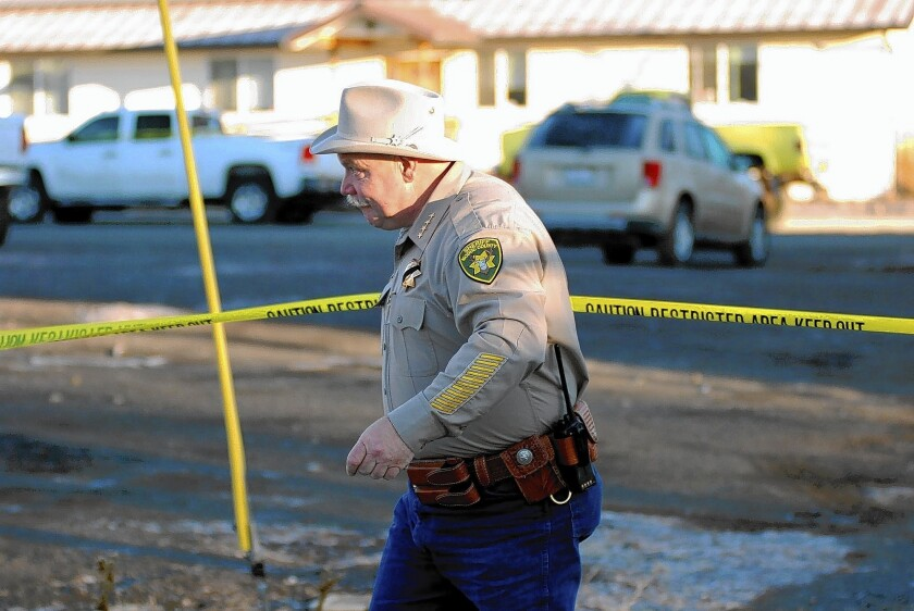 Modoc County Sheriff and Coroner Mike Poindexter surveys the scene Friday at the Cedarville Rancheria headquarters in Alturas, Calif. The day before, four people were shot and killed during a tribal meeting at the headquarters.