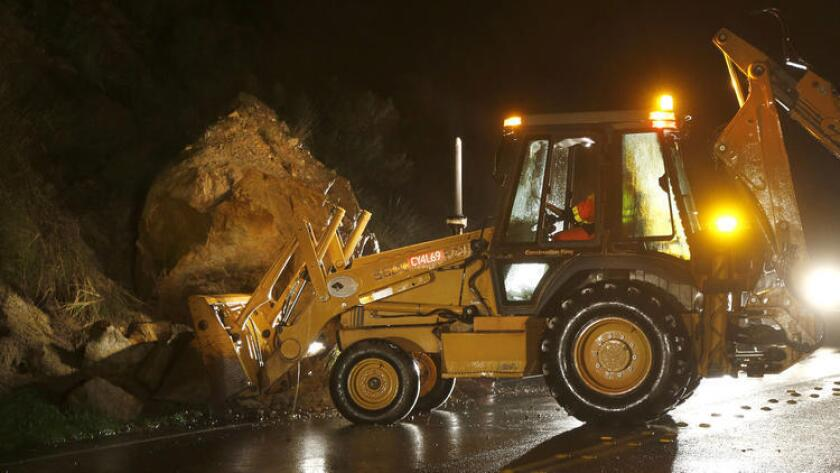 Public work crews clear a road amid storms.