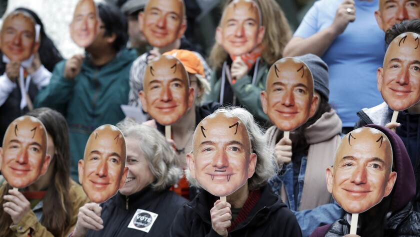 FILE - In this Oct. 31, 2018, file photo, demonstrators hold images of Amazon CEO Jeff Bezos near th