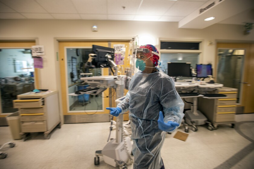 A doctor walks through a medical center in full protective gear.