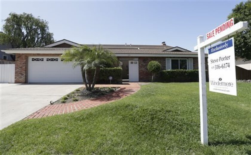 """A home for sale sits behind a sign that reads, """"sale pending,""""in San Diego."""