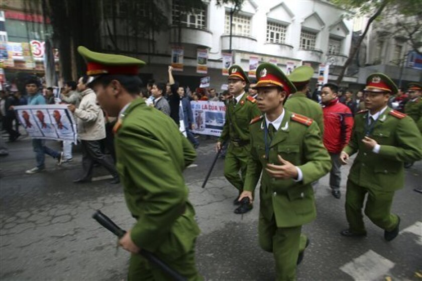 Vietnamese policemen run to block protesters as they march during a demonstration demanding China to stay out of their waters following China's increased activities around the Spratly Islands and other disputed areas, in Hanoi, Vietnam on Sunday, Dec. 9, 2012. Vietnamese police broke up anti-China protests in two cities on Sunday and made about 20 arrests in the first such demonstrations since tensions between the communist neighbors flared anew over rival claims to the oil and gas-rich South China Sea. (AP Photo/Na Son Nguyen)