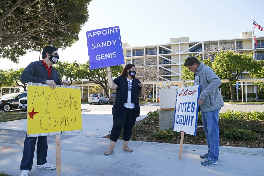 Costa Mesa residents, from left, Ben Chapman, Hengameh Abraham and Dale Luther rally Tuesday at Costa Mesa City Hall.