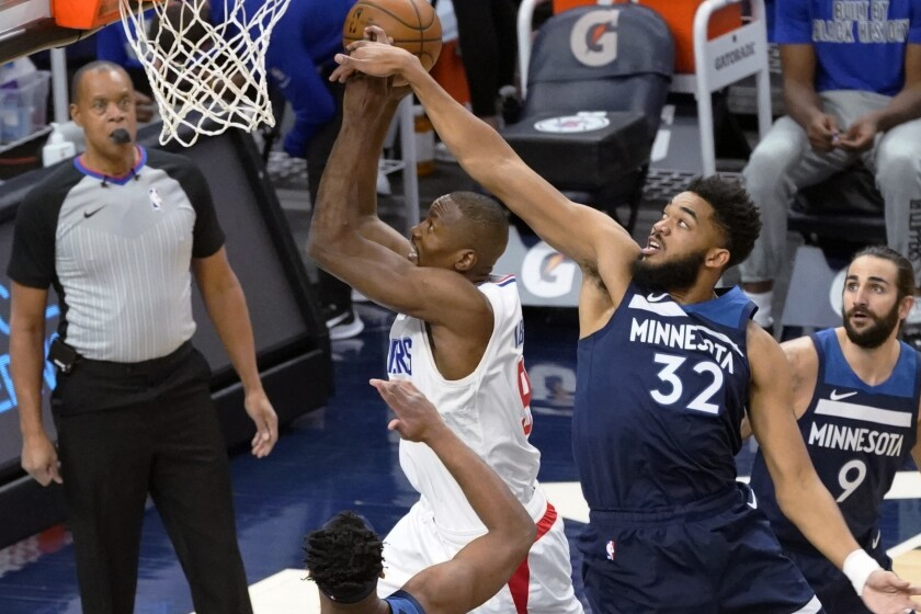 Minnesota Timberwolves' Karl-Anthony Towns (32) attempts to block a shot by Los Angeles Clippers' Serge Ibaka (9) during the first half of an NBA basketball game Wednesday, Feb. 10, 2021, in Minneapolis. (AP Photo/Jim Mone)