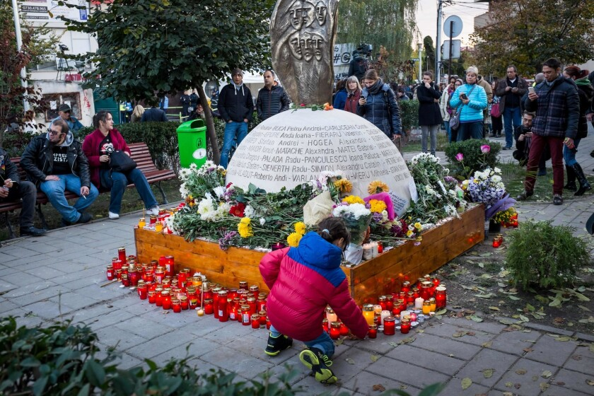 A child lights a candle in front of a monument erected in the memory of the 64 people who were killed when Colectiv club caught fire during a rock concert in October 2015 in Bucharest, Romania.