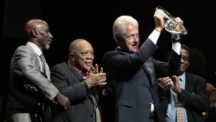 Former President Bill Clinton receives an award and is flanked by Thelonious Monk Jr., left, Quincy Jones and Herbie Hancock.