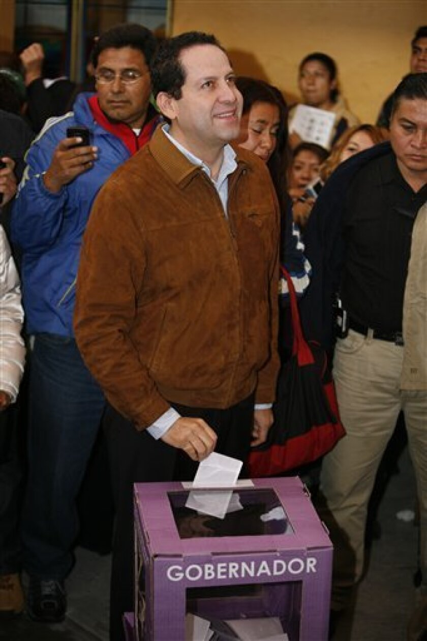 Eruviel Avila, the Institutional Revolutionary Party's (PRI) gubernatorial candidate in the state of Mexico, casts his vote in Ecatepec, Mexico, Sunday July 3, 2011. Avila heads into the closely watched race with a 30 percentage point. The PRI, which has never lost the governorship in more than 80 years, hopes for a commanding victory to create momentum going into the July 2012 national election, where it wants to regain the presidency it lost in 2000 after 71 years of uninterrupted rule. (AP Photo/Marco Ugarte)
