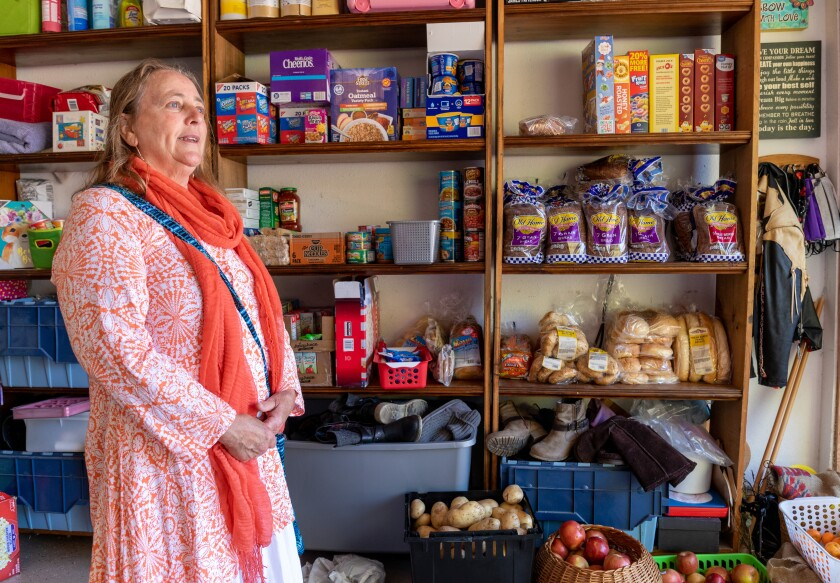 Jannah Loigman in her garage by shelves of food that was donated for the pantry she operated with her husband.