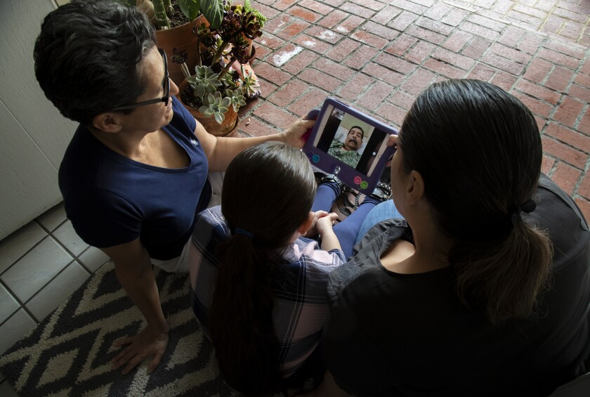 Teresa Gonzalez, left, with her granddaughter Camila, 8, and daughter Mabel, FaceTime with Gonzalez's husband, Francisco.