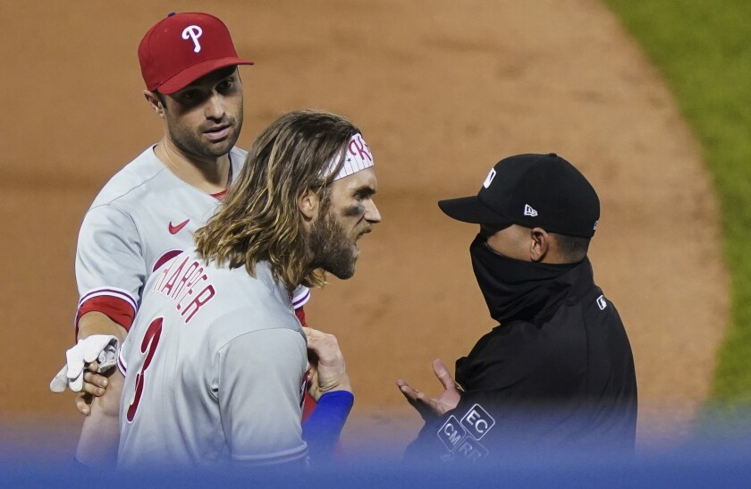 Philadelphia Phillies' Bryce Harper, front left, argues with umpire Roberto Ortiz, right, after Ortiz ejected Harper during the fifth inning of the team's baseball game against the New York Mets, Saturday, Sept. 5, 2020, in New York. (AP Photo/John Minchillo)