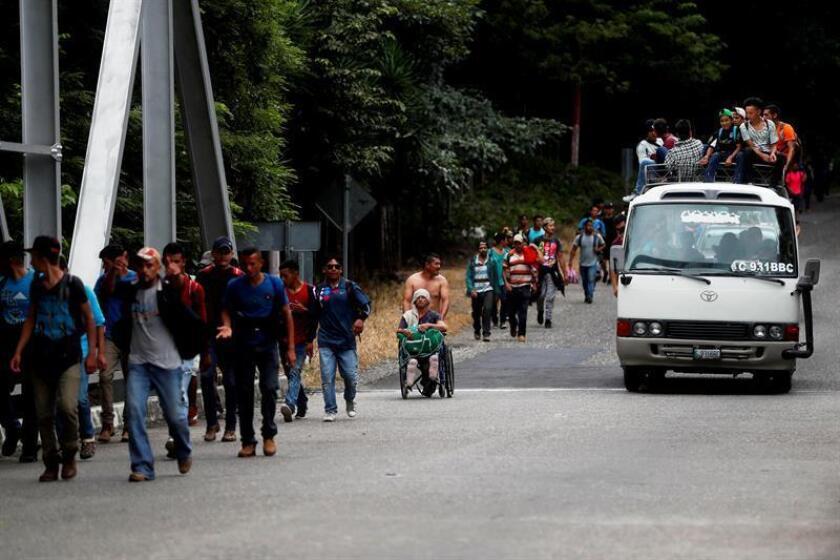 Nery Maldonado (en silla de ruedas) empujado por su amigo Omar Orellana (atrás) migra hoy, martes 16 de octubre de 2018, junto con la caravana de hondureños que espera llegar a Estados Unidos y que ahora continúa su camino por Esquipulas (Guatemala). EFE