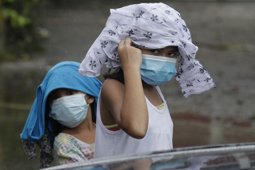 Young girls wearing masks to prevent the spread of the coronavirus place clothes to shelter them from rain due to Typhoon Molave in Pampanga province, northern Philippines on Monday, Oct. 26, 2020. A fast moving typhoon has forced thousands of villagers to flee to safety in provinces. (AP Photo/Aaron Favila)