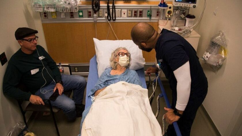 The state Legislature is weighing a measure to end surprise emergency room bills. Above, nurse Reggie Withers tends to flu patient Louise Dominguez of Carson as her son Al Dominguez sits nearby inside the ER at Torrance Memorial Medical Center last year.