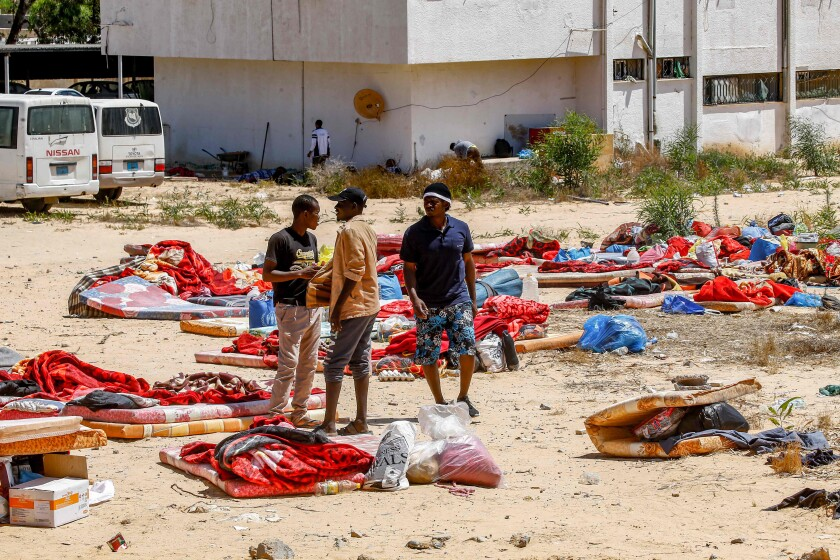 Migrants stand outside a center used by the Libyan Government of National Accord in Tripoli on July 3 following an air strike on a nearby building that killed dozens the night before. The GNA accused Libyan strongman Gen. Khalifa Haftar of being behind the attack.