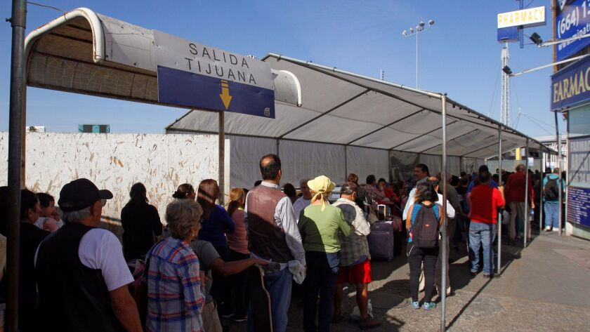 Pedestrians wait in line earlier this month to be inspected at the San Ysidro Port of entry.