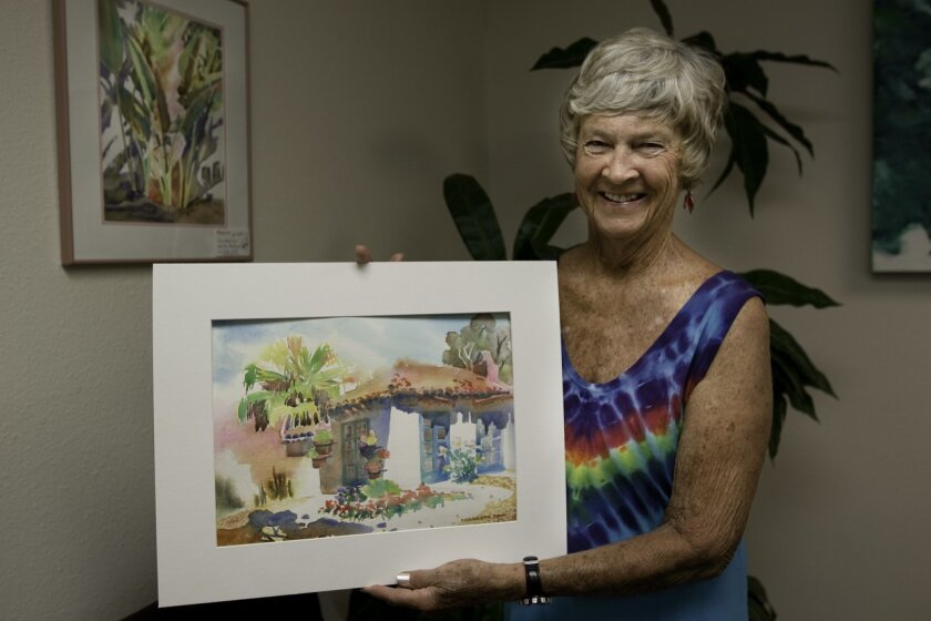 La Jolla painter Charlotte Zinn holds her latest piece, a landscape of the Scotland House in Balboa Park. Zinn likes to paint on Wednesday mornings with a group of fellow artists in the San Diego Watercolor Society. Ashley Mackin