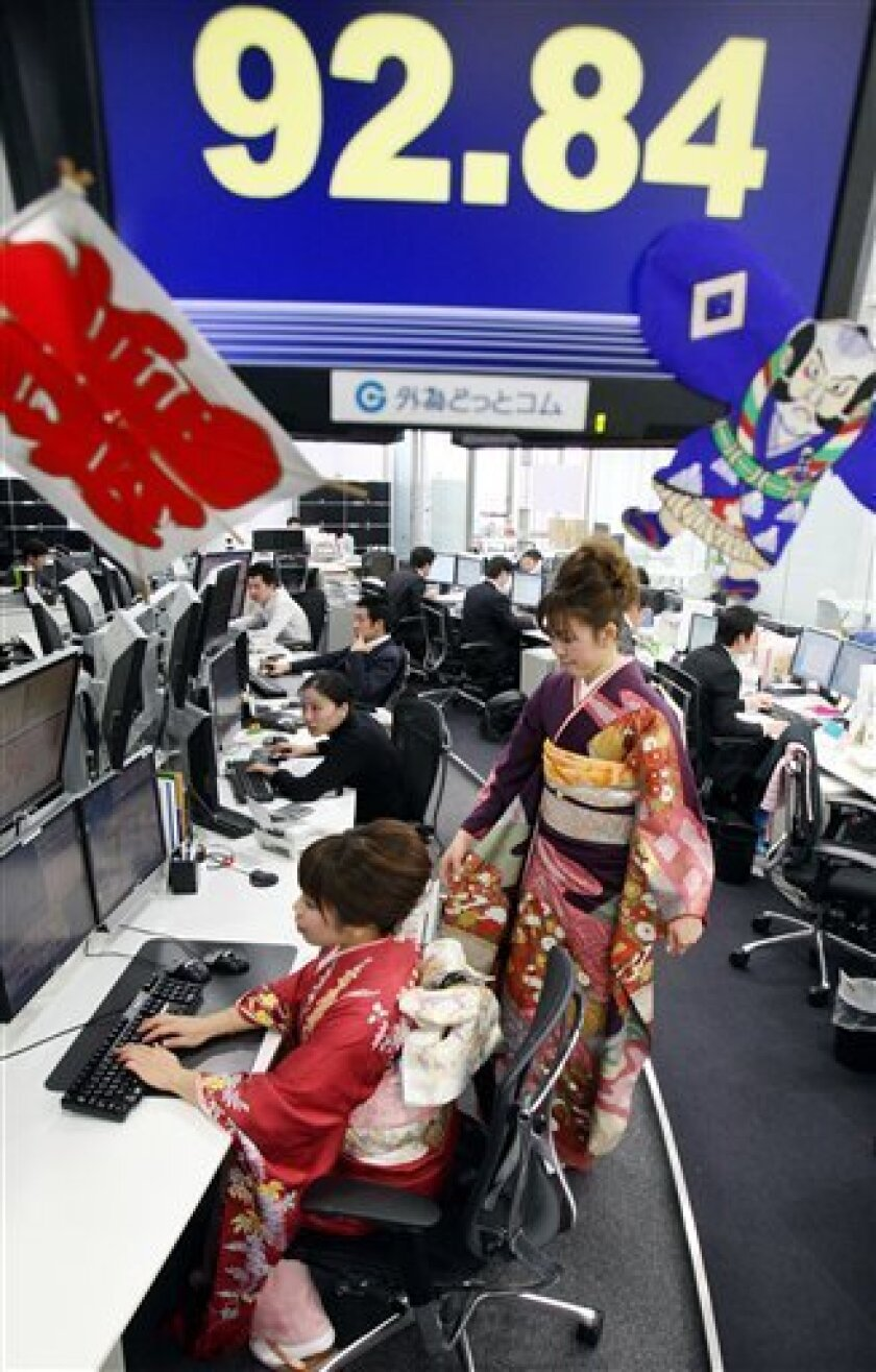 Traders clad in kimonos work at their desk as they start the first business of 2010 at a foreign currency market in Tokyo Jan. 4, 2010. (AP Photo/Koji Sasahara)