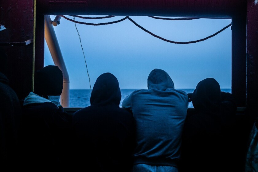 Migrants stand on the deck of the Ocean Viking rescue ship, in the Mediterranean Sea on Sunday, Feb. 7, 2021. A rescue ship with 422 migrants aboard, some of whom tested positive for COVID-19, is heading to Sicily. SOS Mediterranee, the humanitarian group which operates the rescue ship Ocean Viking, told The AP on Sunday that Italy granted the vessel permission to enter the port of Augusta. (Hippolyte/SOS Mediterranee via AP)