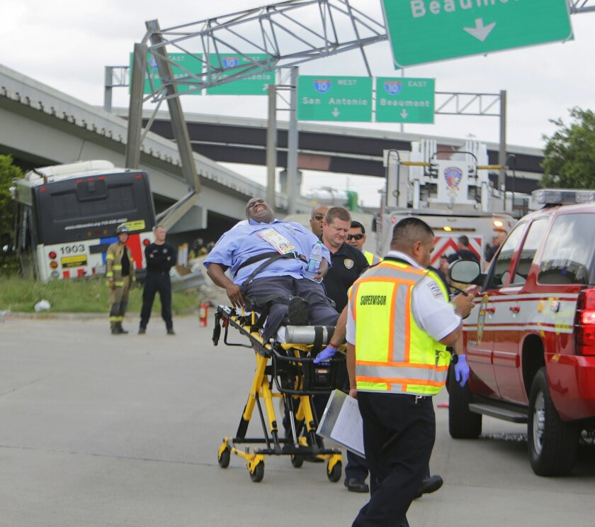 A Metro operator who was riding as a passenger on a Metro bus involved in a crash is removed by emergency workers, Wednesday, June 1, 2016, in Houston. A Houston transit bus hit a pickup truck and slammed into an overhead highway sign, injuring dozens of people. (Mark Mulligan/Houston Chronicle via