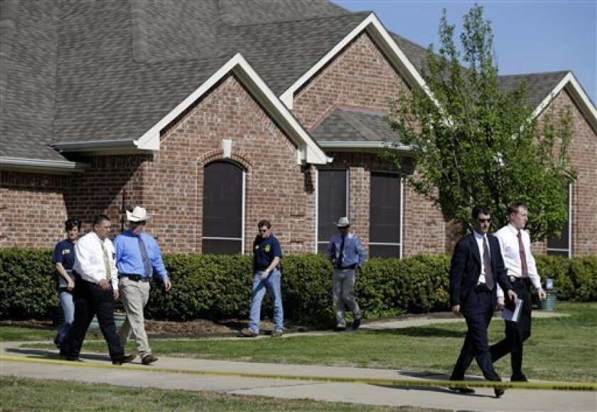 Law enforcement officials walk out of the home of Kaufman District Attorney Mike McLelland Monday, April 1, 2013, near Forney, Texas. McLelland and his wife were both murdered at their home Saturday. (AP Photo/Tony Gutierrez)