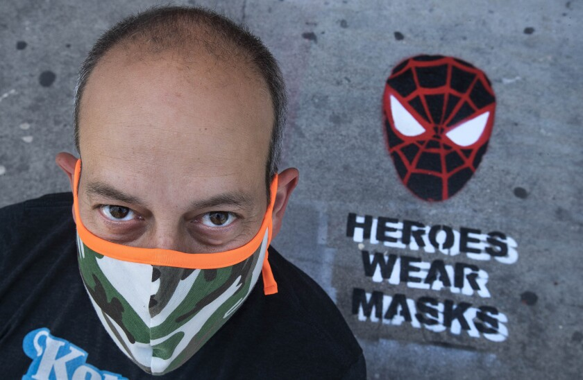Neal Brandenburg poses in front of a Spider-Man mask that he painted.