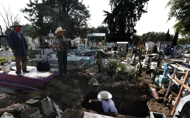 El músico de cementerio Víctor Dzib Cima, de 70 años, toca su acordeón mientras espera clientes cuando trabajadores de cementerio retiran ataúdes de tumbas que pertenecen a familiares que dejaron de pagar alquiler en el cementerio San Nicolás Tolentino, en donde ha trabajado a cambio de propinas durante 22 años en la alcaldía Iztapalapa en Ciudad de México el viernes 22 de mayo de 2020. El cementerio hace espacio para más entierros durante la pandemia de COVID-19 y se acostumbra que los cementerios en México alquilen, en lugar de vender, los sitios de entierro. (AP Foto/Marco Ugarte)