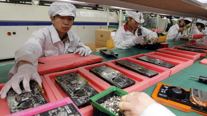 FILE - In this May 26, 2010 file photo, staff members work on the production line at the Foxconn com