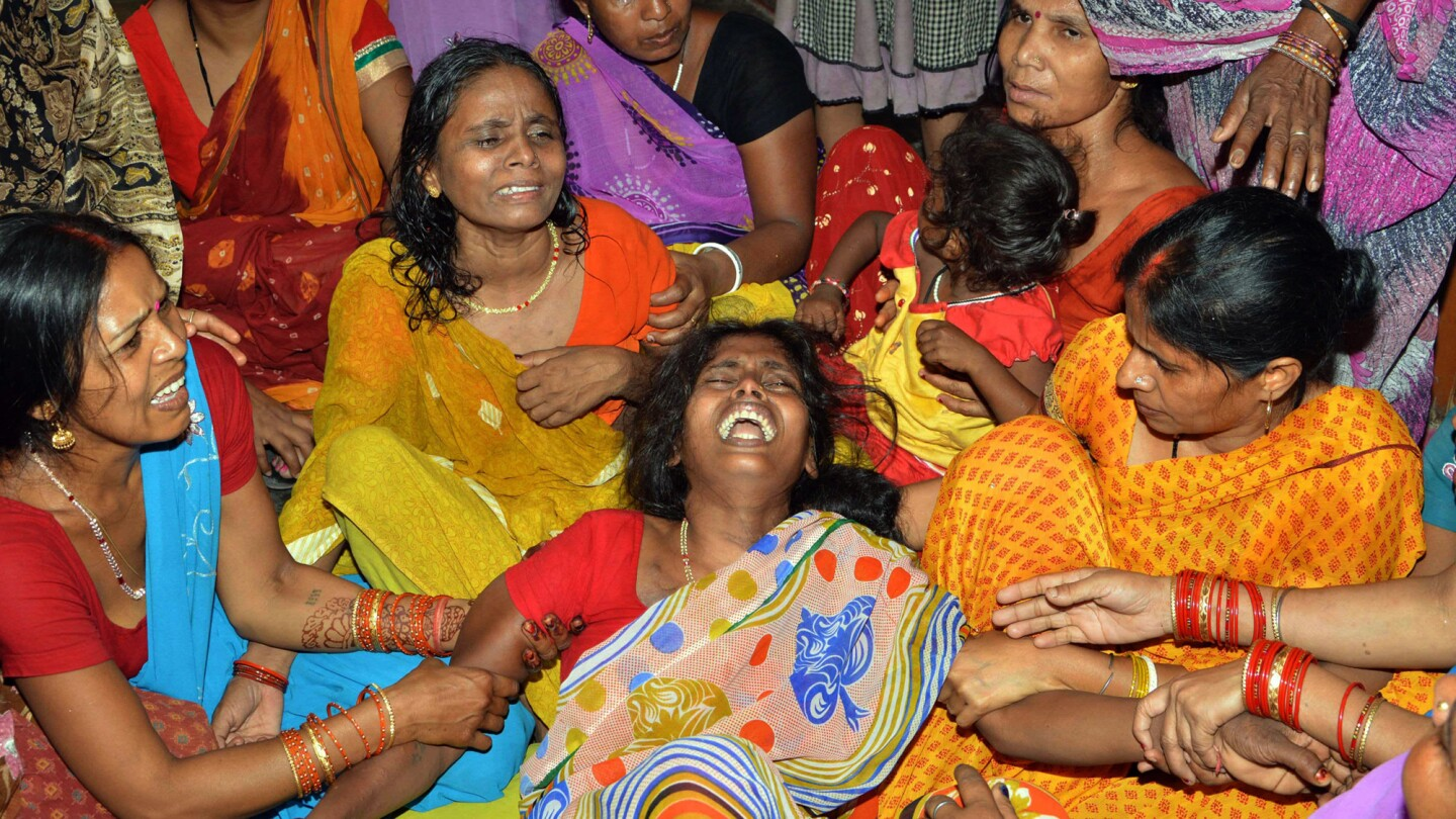 Friends and relatives surround a woman whose husband was killed May 12 on the outskirts of Patna, India, after a 7.3 earthquake struck Nepal.