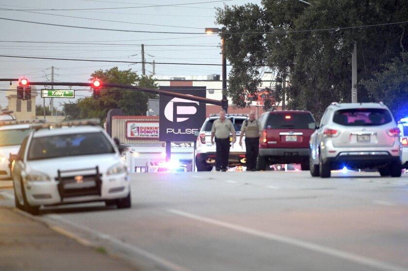 Police cars surround the Pulse Orlando nightclub, the scene of a fatal shooting, in Orlando, Fla., Sunday, June 12, 2016. (AP Photo/Phelan M. Ebenhack)