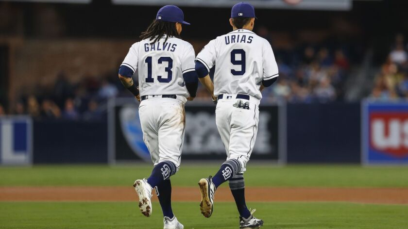 Shortstop Freddy Galvis and second baseman Luis Urias jog to their positions before Tuesday's fourth inning.