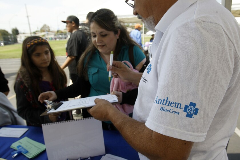 An Anthem Blue Cross representative works in a booth at the East Los Angeles Health Fair held at David Wark Griffith Middle School last September.