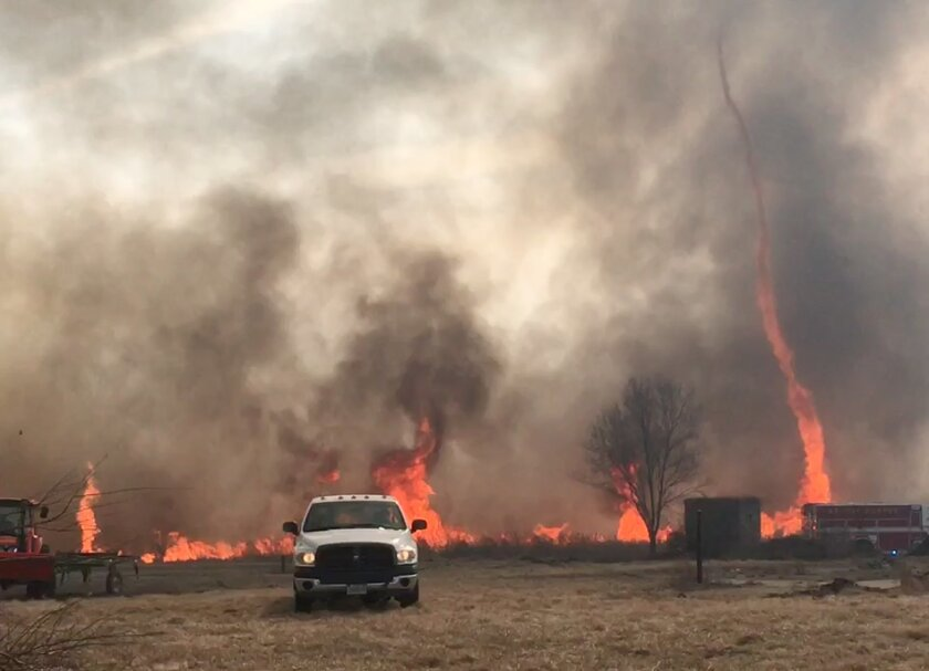 In this image made from a Feb. 18, 2016 video by Dean Cull, deputy chief of the Southern Platte Fire Protection District, a twisting fire, also known as a fire tornado, shoots up in the air as the grass fires spread on the field in Platte County, Mo. Firefighters in northwest Missouri are continuin