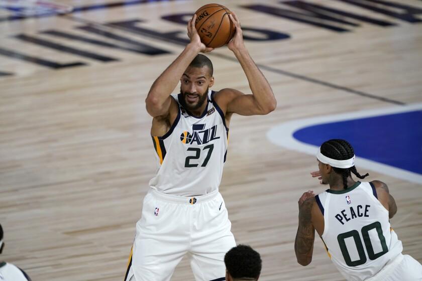 Utah Jazz's Rudy Gobert (27) looks to pass as teammate Jordan Clarkson (00) watches.