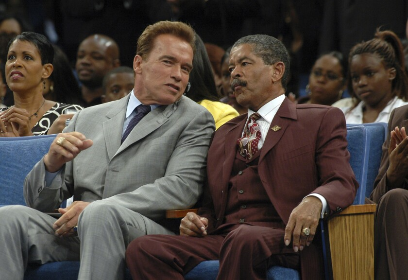 Arnold Schwarzenegger and Frederick K.C. Price sit next to each other