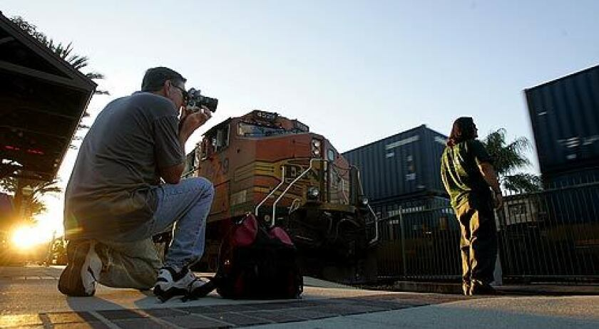 Jeffrey Bass photographs a freight-train brakeman at the Fullerton train station. Bass is among avid rail fans who visit the station regularly to watch and take pictures of the trains. The Chatsworth crash -- and revelations that engineer Robert Sanchez was in contact with rail fans while on the job -– stirred an angry backlash against train hobbyists.