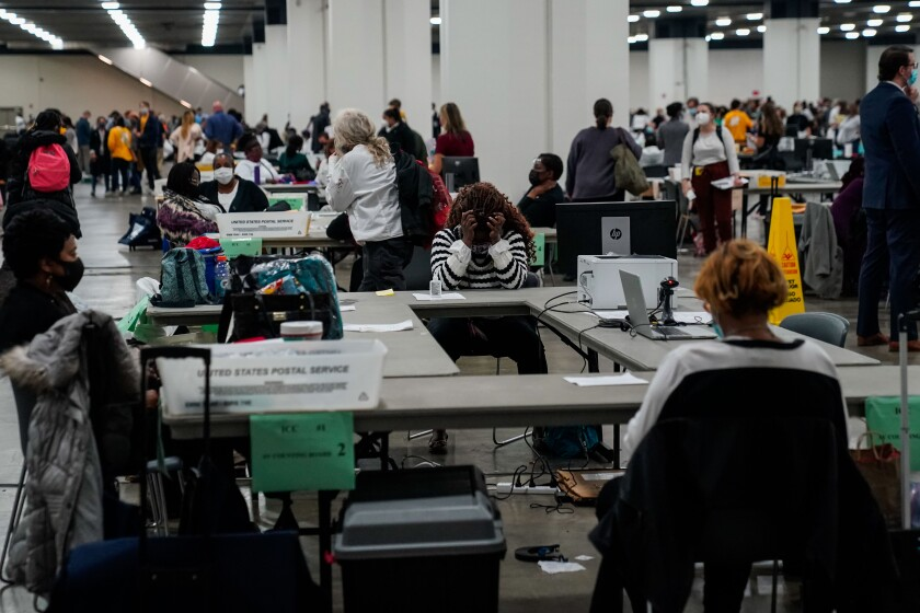 Election workers and observers process a surge in mail ballots in Detroit on Wednesday.