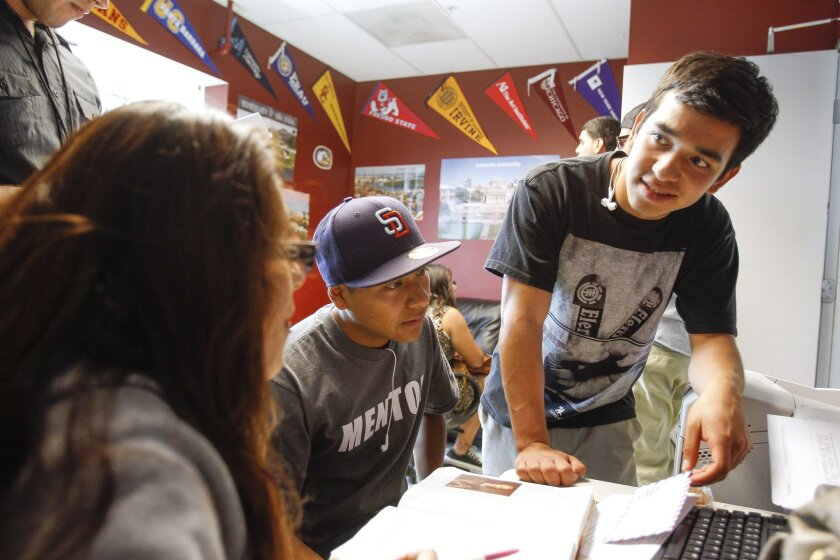 Garcia (right) talks to students during the Project REACH after-school program. Among its services, the program provides mentoring, college and career preparation and homework help.