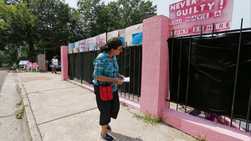 Pam Miller, of Pro Life Mississippi, walks along the fence surrounding the Jackson Women's Health Organization clinic near downtown Jackson, Miss. in 2015. The facility is the only legal abortion clinic in the state.