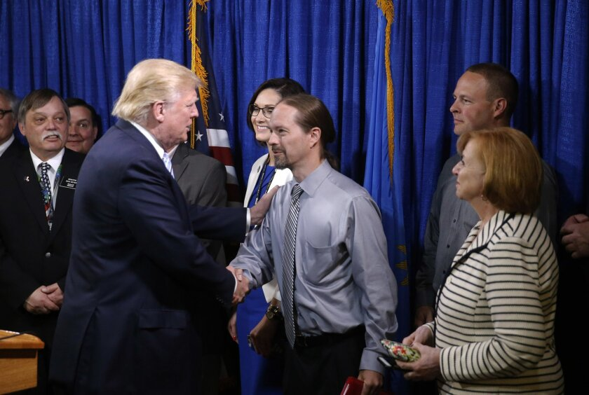 Republican presidential candidate Donald Trump, right, shakes hands with John Trandem, one of the 22 delegates from North Dakota to the Republican National Convention, who are the core of delegates that elevated Trump over the 1237 needed for the GOP's presidential nomination, Thursday, May 26, 201