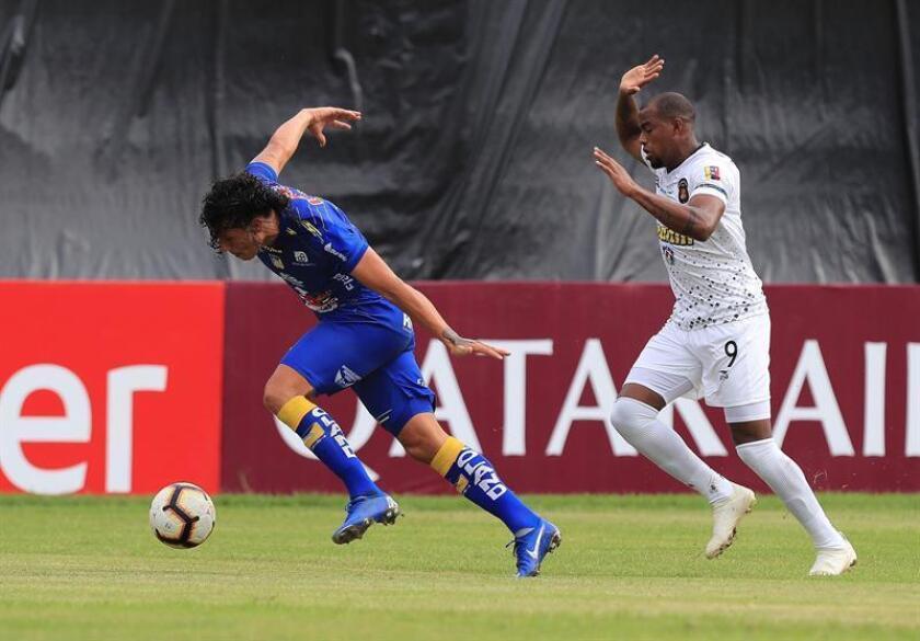 El jugador de Delfín Williams Riveros (i) disputa el balón con Carlos Espinoza (d) de Caracas durante un partido de la Copa Libertadores entre Delfín de Ecuador y Caracas de Venezuela, en el estadio Jocay en Manta (Ecuador). EFE