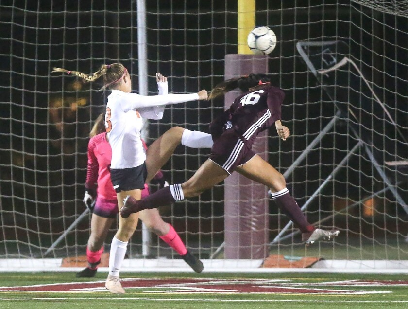 Laguna Beach High's Reilyn Turner heads the ball in for the game's first goal against Huntington Bea