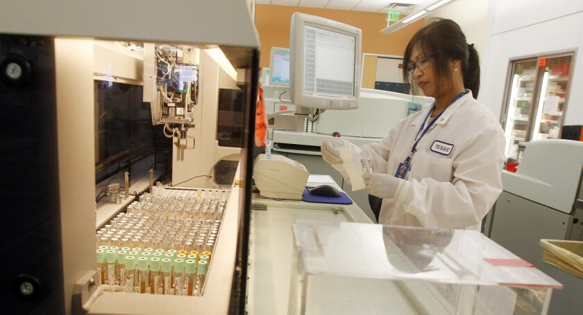 Clinical lab technician assistant Tessie Jacinto works in the centralized Chemistry testing lab for Scripps Health on Friday in San Diego, California.