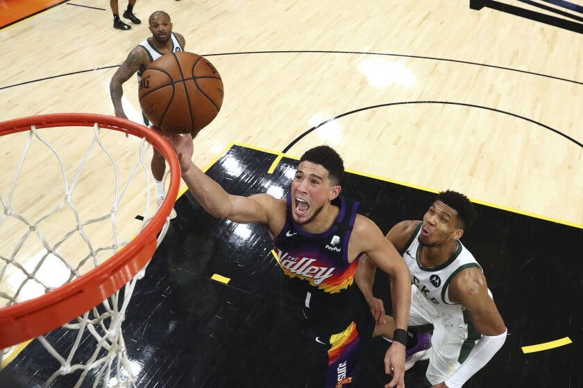 FILE - In this Saturday, July 17, 2021, file photo, Phoenix Suns guard Devin Booker (1) shoots past Milwaukee Bucks forward Giannis Antetokounmpo, right, during the second half of Game 5 of basketball's NBA Finals, in Phoenix. On Sunday, Sept. 26, 2021, the Suns announced that Booker will miss the start of training camp after being placed in the league's health and safety protocol. (Mark J. Rebilas/Pool Photo via AP, File)