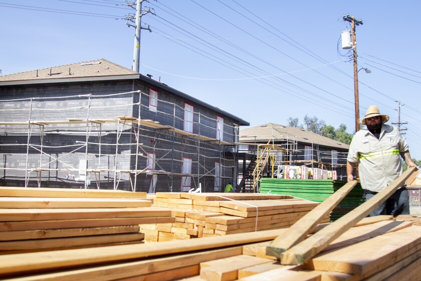 Operator Chris Freeman moves wood at the construction site for two new dorms at ECTLC in El Cajon.