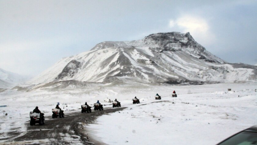 A group of ATVs crosses the snow on a gray winter day in Iceland.