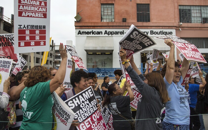 American Apparel workers protest the company's planned layoffs and store closures in front of the clothier's headquarters in downtown Los Angeles on Wednesday.